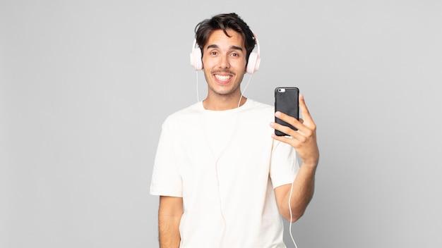 Junger hispanischer mann, der mit kopfhörern und smartphone glücklich und angenehm überrascht aussieht