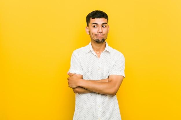 Junger hispanischer mann, der mit sarkastischem ausdruck unglücklich schaut.