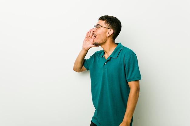 Junger hispanischer mann, der palme nahe geöffnetem mund schreit und hält.