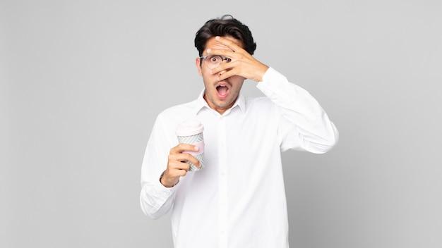 Junger hispanischer mann, der schockiert, verängstigt oder verängstigt aussieht, das gesicht mit der hand bedeckt und einen kaffee zum mitnehmen hält
