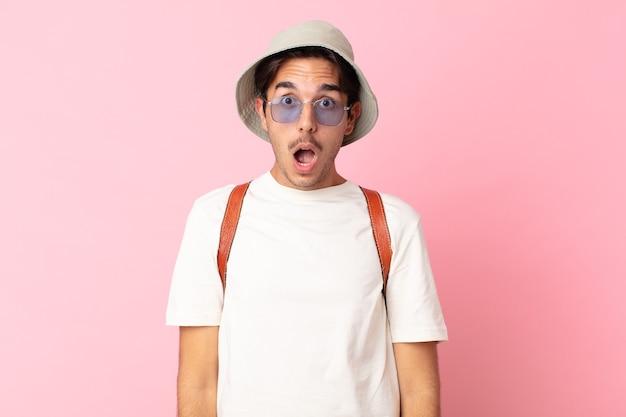 Junger hispanischer mann, der sehr schockiert oder überrascht aussieht. sommerkonzept