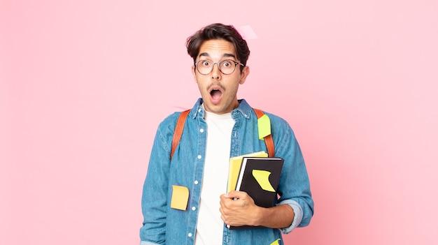 Junger hispanischer mann, der sehr schockiert oder überrascht aussieht. studentisches konzept