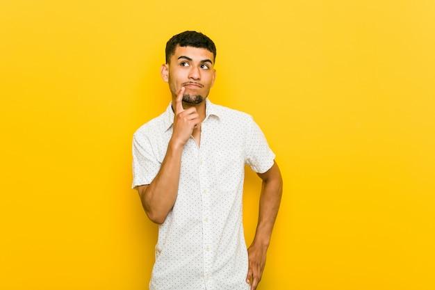 Junger hispanischer mann, der seitlich mit zweifelhaftem und skeptischem ausdruck schaut.