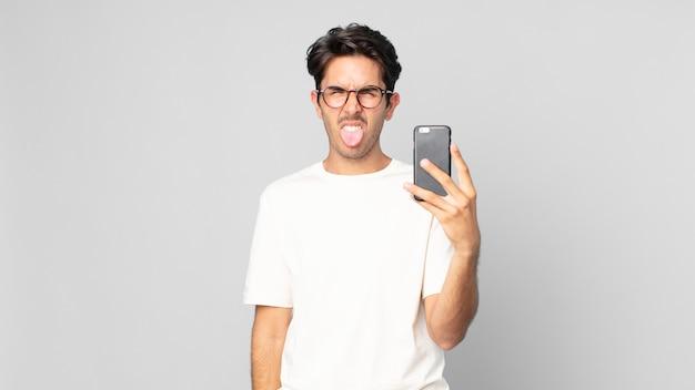 Junger hispanischer mann, der sich angewidert und irritiert fühlt und die zunge herausstreckt und ein smartphone hält