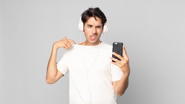 Junger hispanischer mann, der sich gestresst, ängstlich, müde und frustriert mit kopfhörern und smartphone fühlt
