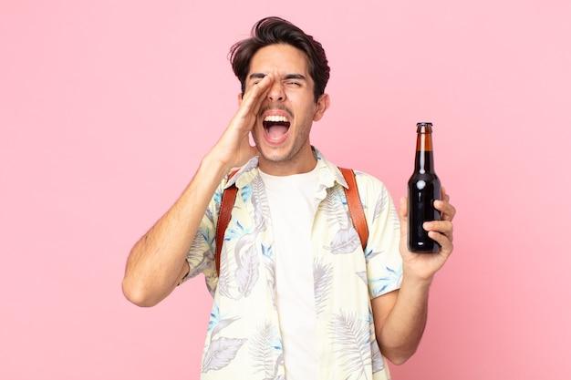 Junger hispanischer mann, der sich glücklich fühlt, mit den händen neben dem mund einen großen schrei ausspricht und eine flasche bier hält