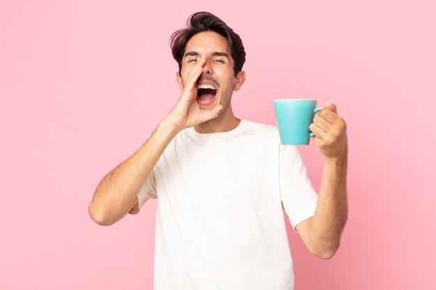 Junger hispanischer mann, der sich glücklich fühlt, mit den händen neben dem mund einen großen schrei ausspricht und eine kaffeetasse hält