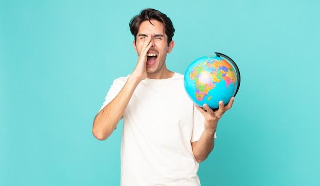 Junger hispanischer mann, der sich glücklich fühlt, mit den händen neben dem mund einen großen schrei ausspricht und eine weltkugelkarte hält