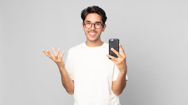 Junger hispanischer mann, der sich glücklich fühlt, überrascht, eine lösung oder idee zu realisieren und ein smartphone zu halten