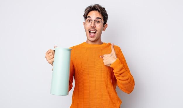Junger hispanischer mann, der sich glücklich fühlt und mit aufgeregter auf sich selbst zeigt. thermos-konzept