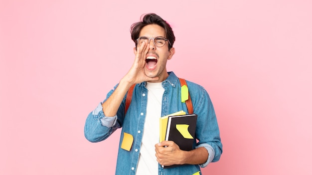 Junger hispanischer mann, der sich glücklich fühlt und mit den händen neben dem mund einen großen schrei ausspricht. studentisches konzept