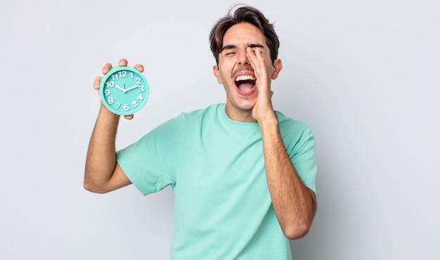 Junger hispanischer mann, der sich glücklich fühlt und mit den händen neben dem mund einen großen schrei ausspricht. weckerkonzept