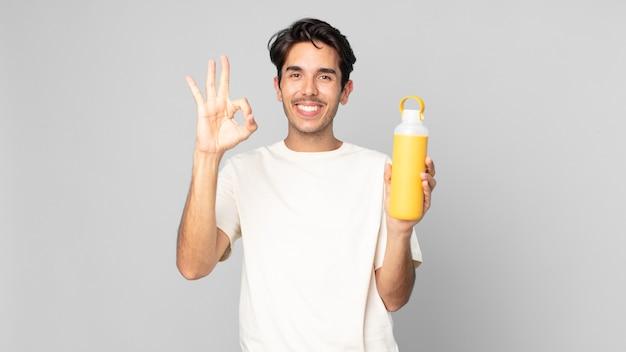 Junger hispanischer mann, der sich glücklich fühlt und zustimmung mit einer guten geste mit einer kaffee-thermoskanne zeigt