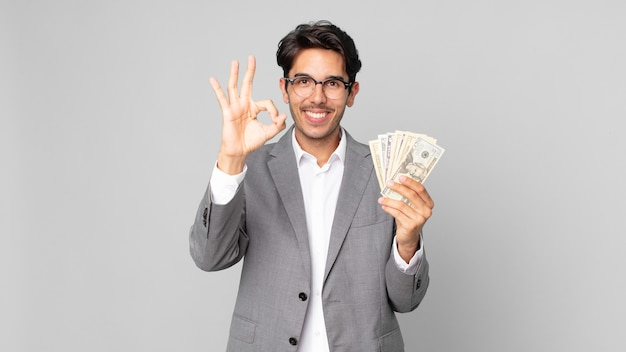 Junger hispanischer mann, der sich glücklich fühlt und zustimmung mit einer okayen geste zeigt