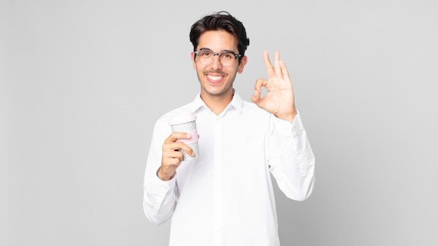 Junger hispanischer mann, der sich glücklich fühlt, zustimmung mit okayer geste zeigt und einen kaffee zum mitnehmen hält