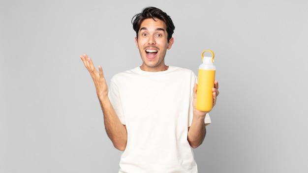 Junger hispanischer mann, der sich mit einer kaffee-thermoskanne glücklich und erstaunt über etwas unglaubliches fühlt