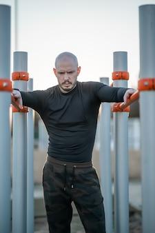Junger hispanischer mann, der sich nach dem training an den reckstangen ausruht