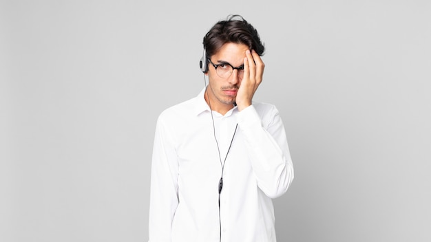 Junger hispanischer mann, der sich nach einem ermüdenden gefühl gelangweilt, frustriert und schläfrig fühlt. telemarketing-konzept