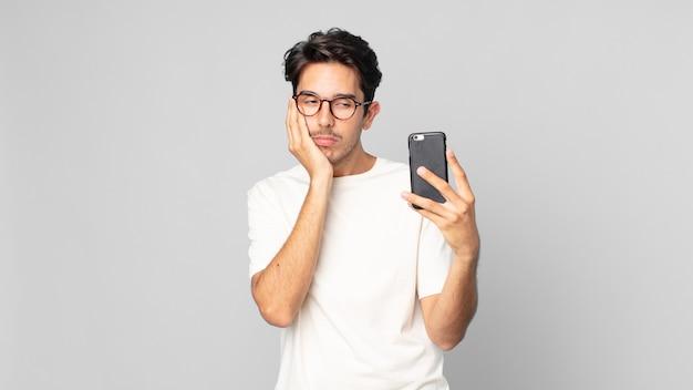 Junger hispanischer mann, der sich nach einem ermüdenden und halten eines smartphones gelangweilt, frustriert und schläfrig fühlt