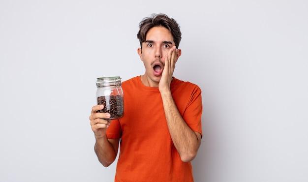 Junger hispanischer mann, der sich schockiert und verängstigt fühlt. kaffeebohnen-konzept