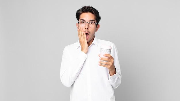 Junger hispanischer mann, der sich schockiert und verängstigt fühlt und einen kaffee zum mitnehmen hält?