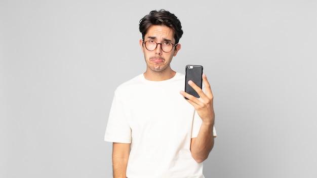 Junger hispanischer mann, der sich traurig und weinerlich mit einem unglücklichen blick fühlt und weint und ein smartphone hält