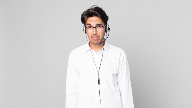 Junger hispanischer mann, der sich traurig und weinerlich mit einem unglücklichen blick und weinen fühlt. telemarketing-konzept