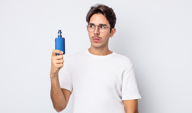 Junger hispanischer mann, der sich traurig, verärgert oder wütend fühlt und zur seite schaut. konzept des rauchverdampfers