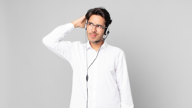 Junger hispanischer mann, der sich verwirrt und verwirrt fühlt und den kopf kratzt. telemarketing-konzept