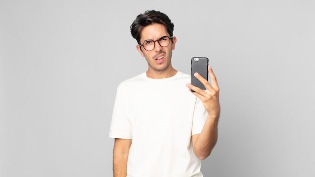 Junger hispanischer mann, der sich verwirrt und verwirrt fühlt und ein smartphone hält