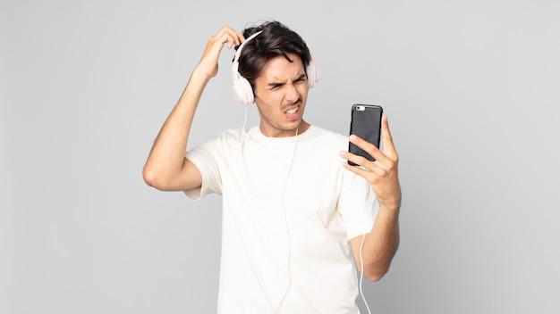 Junger hispanischer mann, der sich verwirrt und verwirrt fühlt und sich mit kopfhörern und smartphone am kopf kratzt