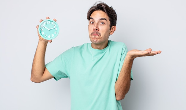 Junger hispanischer mann, der sich verwirrt und verwirrt fühlt und zweifelt. weckerkonzept