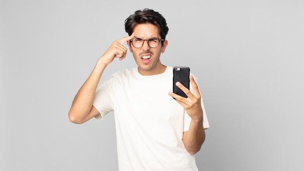 Junger hispanischer mann, der sich verwirrt und verwirrt fühlt, zeigt, dass sie verrückt sind und ein smartphone halten