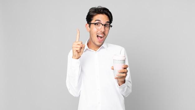 Junger hispanischer mann, der sich wie ein glückliches und aufgeregtes genie fühlt, nachdem er eine idee realisiert und einen kaffee zum mitnehmen gehalten hat