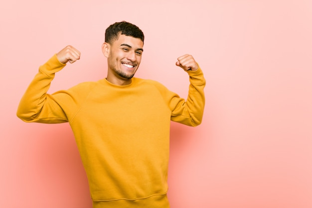 Junger hispanischer mann, der stärkegeste mit den armen, symbol der weiblichen energie zeigt