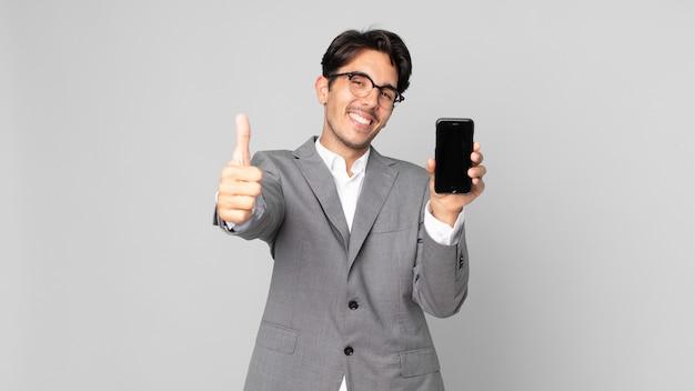 Junger hispanischer mann, der stolz ist, positiv mit daumen nach oben lächelt und ein smartphone hält