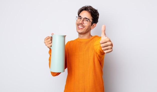 Junger hispanischer mann, der stolz ist und positiv mit daumen nach oben lächelt. thermos-konzept