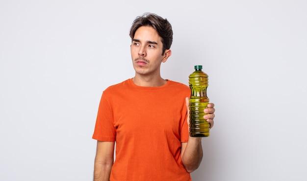 Junger hispanischer mann, der traurig, verärgert oder wütend ist und zur seite schaut. olivenöl konzept