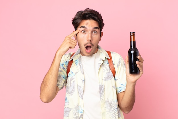 Junger hispanischer mann, der überrascht aussieht, einen neuen gedanken, eine neue idee oder ein neues konzept realisiert und eine flasche bier hält