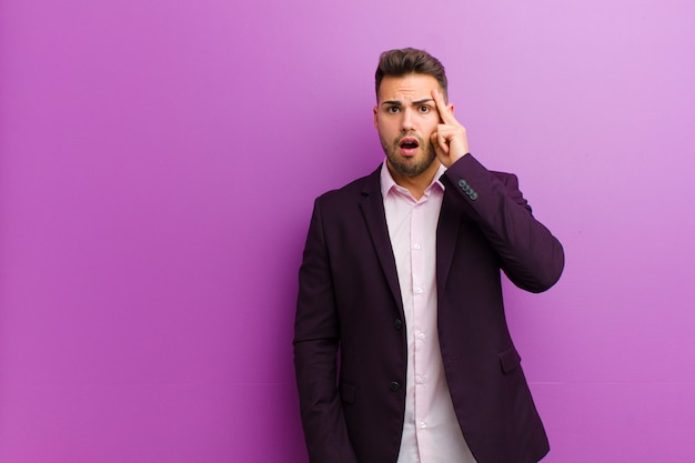 Junger hispanischer mann, der überrascht, mit offenem mund, entsetzt schaut und einen neuen gedanken, eine idee oder ein konzept verwirklicht