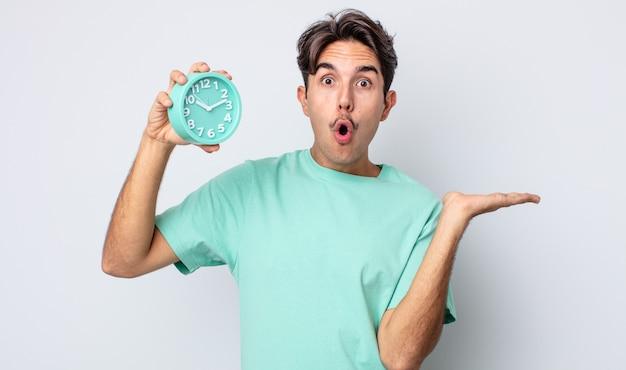 Junger hispanischer mann, der überrascht und schockiert aussieht, mit gesenktem kiefer, der einen gegenstand hält. weckerkonzept