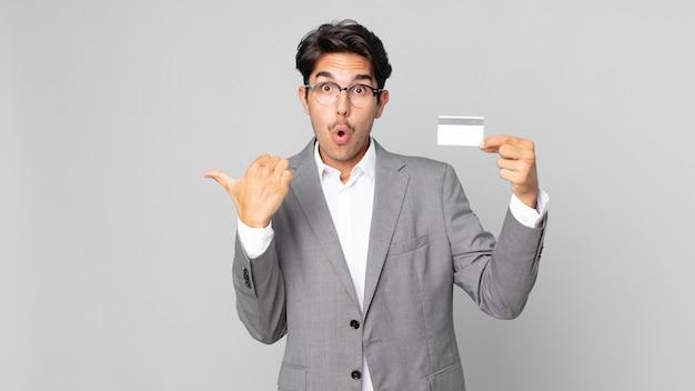Junger hispanischer mann, der ungläubig ausschaut und eine kreditkarte hält