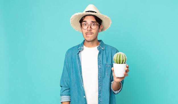 Junger hispanischer mann, der verwirrt und verwirrt aussieht und einen kaktus hält