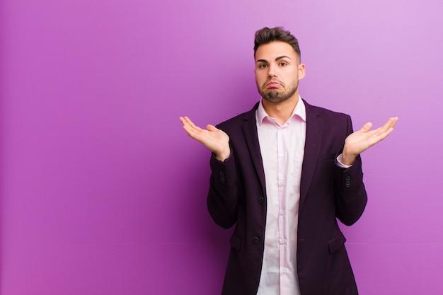 Junger hispanischer mann, der verwirrt und verwirrt sich fühlt, verschiedene wahlen mit lustigem ausdruck zweifelt, belastet oder wählt