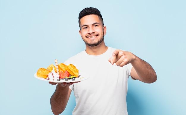 Junger hispanischer mann, der zeigt oder zeigt. waffeln konzept