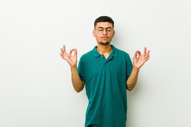Junger hispanischer mann entspannt sich nach hartem arbeitstag, sie führt yoga durch.