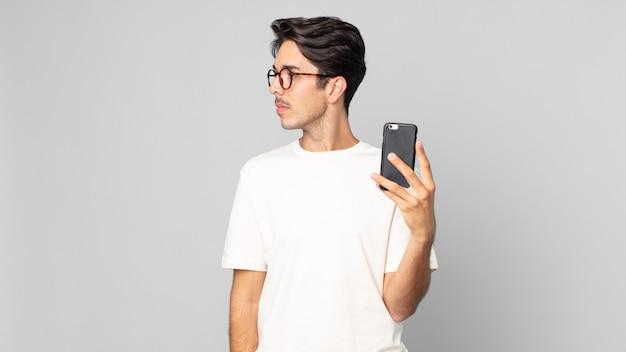 Junger hispanischer mann in der profilansicht, der nachdenkt, sich vorstellt oder träumt und ein smartphone hält
