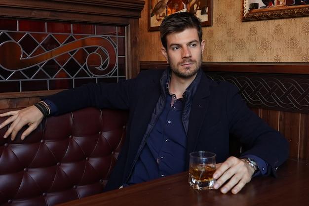 Junger hispanischer mann in einem formellen outfit, das an einem restaurant sitzt und whisky trinkt