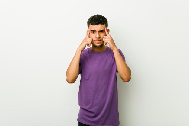 Junger hispanischer mann konzentrierte sich auf eine aufgabe und hielt die zeigefinger, die kopf zeigen
