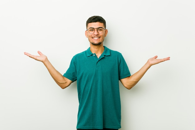 Junger hispanischer mann macht skala mit den armen, fühlt sich glücklich und überzeugt.